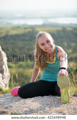 Fit woman stretching her leg to warm up outdoor. - stock photo
