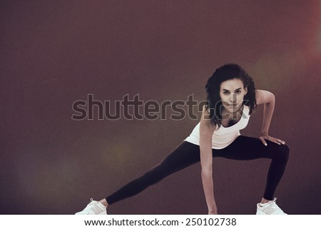 Fit woman stretching her legs against grey - stock photo