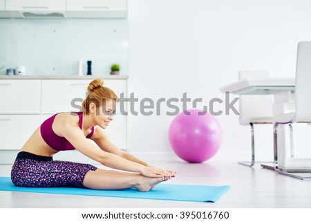 Fit woman stretching on exercise mat at home