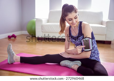 Fit woman stretching on exercise mat at home in the living room - stock photo