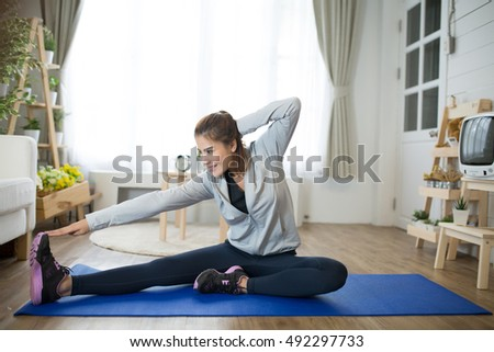 Fit Woman Stretching On Exercise Mat At Home In The Living Roomflare Light