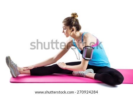 Fit woman stretching on exercise mat on white background - stock photo
