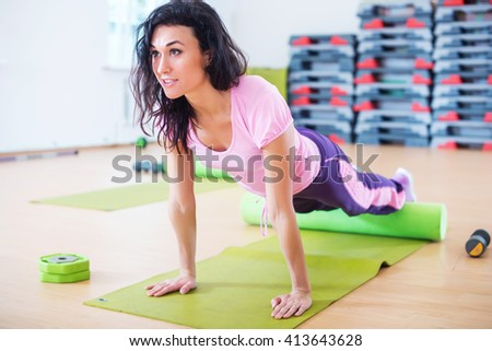 Fit woman stretching on floor using foam roller doing plank exercise, push ups. - stock photo