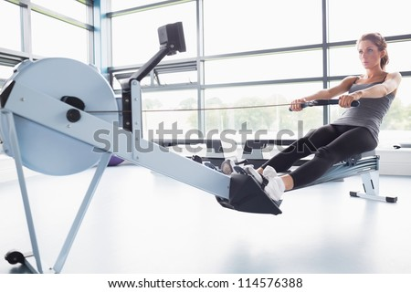 Fit woman training on row machine in gym - stock photo