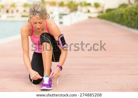 Fit woman tying sports shoe before morning exercise - stock photo