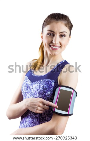 Fit woman using smartphone in armband on white background
