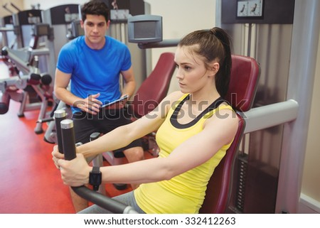 Fit woman using weights machine with trainer at the gym