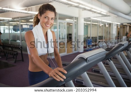 Fit woman wearing towel around shoulders on the treadmill at the gym - stock photo
