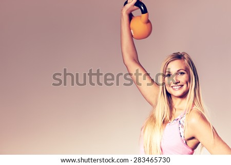Fit woman wearing workout clothes smiling at camera and lifting a kettlebell. Image with copyspace for text. - stock photo