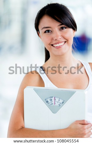 Fit woman with a scale at the gym - stock photo