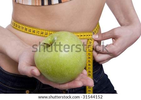Fit woman with measure tape isolated over white. Weight loss and healthy lifestyle concept. Girl measuring waist with a tape measure. Isolated. Woman hold apple in hand. Waist is 65.5 centimeters. - stock photo