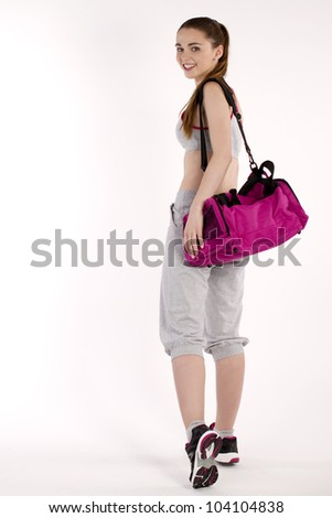 Fit woman with sports bag ready for workout. Isolated on white background.