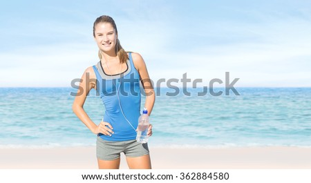 Fit woman with water against beach scene