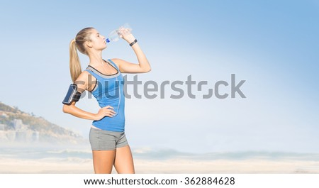 Fit woman with water against beautiful beach and blue sky