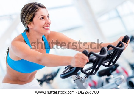 Fit woman working out at the gym and looking happy - stock photo