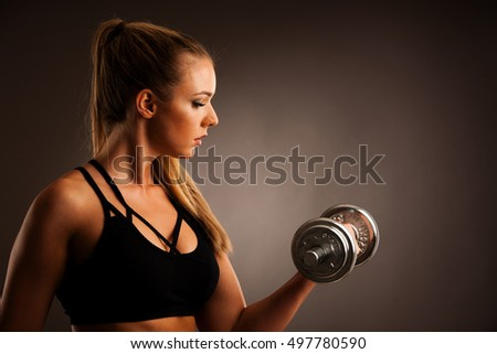 fit woman workout with dumbbells in gym studio photography of a bikini fitness competitor