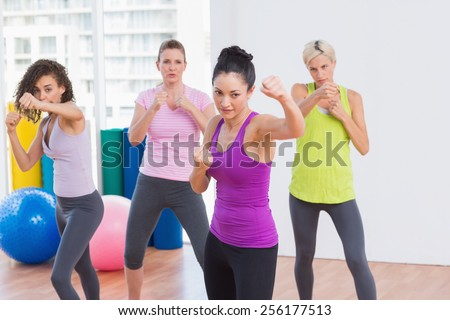 Fit women boxing in air at fitness studio