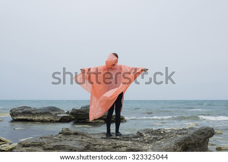 Fit women dressed in raincoat standing with outstretched arms while enjoying beautiful sea landscape in a rainy day, female runner relaxing after morning jog on the beach in cloudy autumn weather - stock photo
