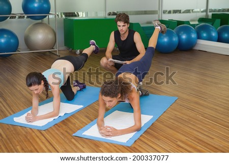Fit women in pilates position with trainer watching at the gym