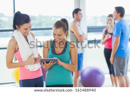 Fit women looking at digital table with friends chatting in background in bright exercise room - stock photo