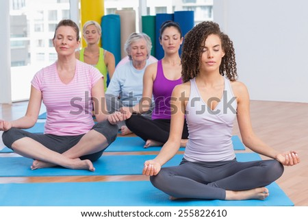 Fit women practicing lotus position in gym class - stock photo