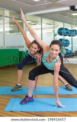 Fit women stretching on exercise mats at the gym