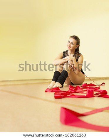 Fit young adult woman with red ribbon at yellow wall background with reflection on mirror Cut girl looking with smiley face at camera  - stock photo