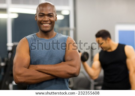 fit young african man posing with arms folded in gym - stock photo