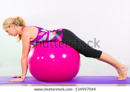 Fit young blonde pilates instructor showing different exercises with basic sport equipment including ball and yoga mat