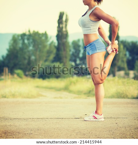 Fit young Caucasian woman stretching her leg after jogging. Fit runner girl in blue shorts stretch after workout outdoors in park on sunny summer day. - stock photo