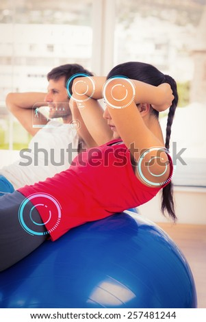 Fit young couple exercising on fitness balls in gym against fitness interface - stock photo