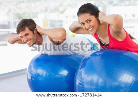 Fit young couple exercising on fitness balls in the bright gym - stock photo
