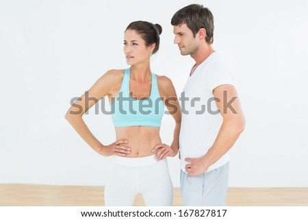 Fit young couple looking away in the fitness studio