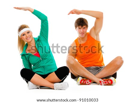 Fit young female and guy in sportswear sitting on floor and making exercises isolated on white