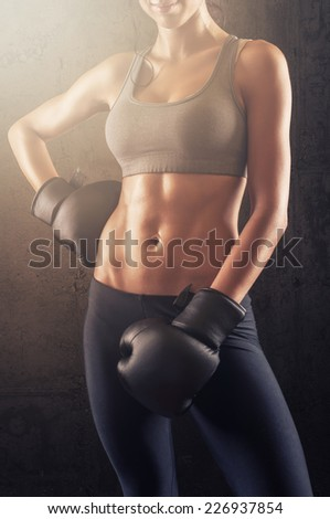 Fit young fitness woman with boxing gloves posing and showing muscular body - stock photo