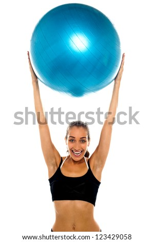 Fit young lady holding up big blue exercise ball above her head.