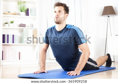 Fit Young Man Doing his Daily Press Up Exercise on a Fitness Mat at Home Alone. - stock photo