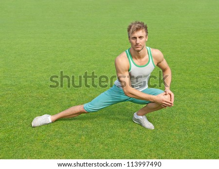 Fit young man exercising outdoors on green field.