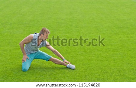 Fit young man exercising outdoors on green sports field.