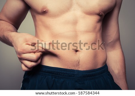 Fit young man pinching the fat on his stomach - stock photo