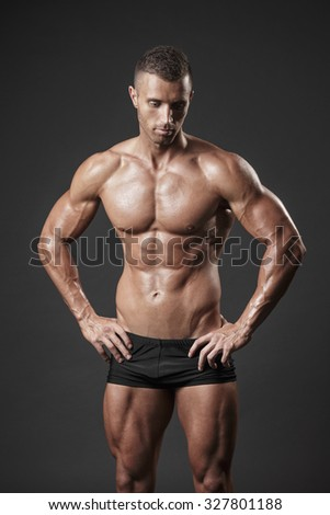 Fit young man posing and showing his muscles  - stock photo