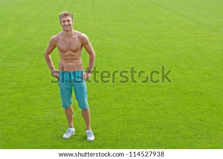 Fit young man standing on green playing field, smiling.