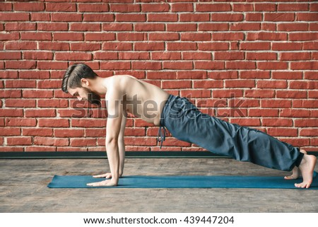Fit young man with a beard wearing trousers doing yoga position on blue matt at wall background, copy space, portrait, plank. - stock photo