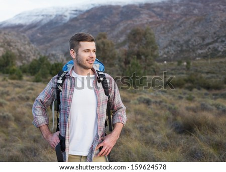 Fit young man with backpack standing on forest landscape