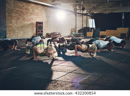 Fit young people doing pushups in a gym looking focused - stock photo