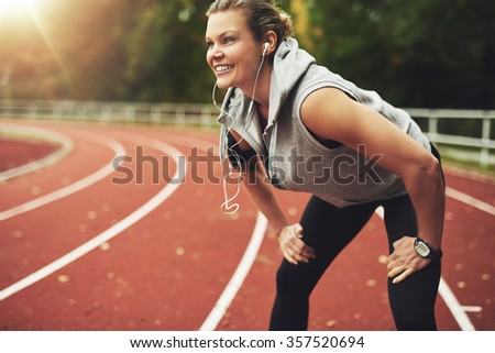 Fit young sportswoman on track field smiling and listening to music - stock photo
