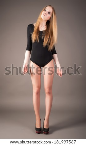 Fit young woman doing standing at grey background