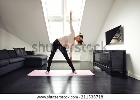 Fit young woman doing stretching exercise at her home. Healthy caucasian female model exercising in living room over exercise mat.