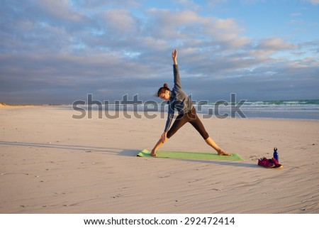 Fit young woman in a yoga pose on her yoga mat at sunrise on a beach - stock photo