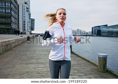 Fit young woman running on the boardwalk along river. Caucasian female athlete training outdoors by the waterfront. - stock photo